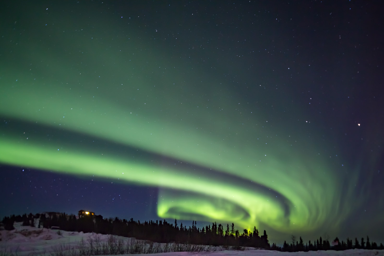 A Limited Edition, Fine Art photograph of a swirling green aurora over a hill and small cabin in Fairbanks, Alaska.  Available...