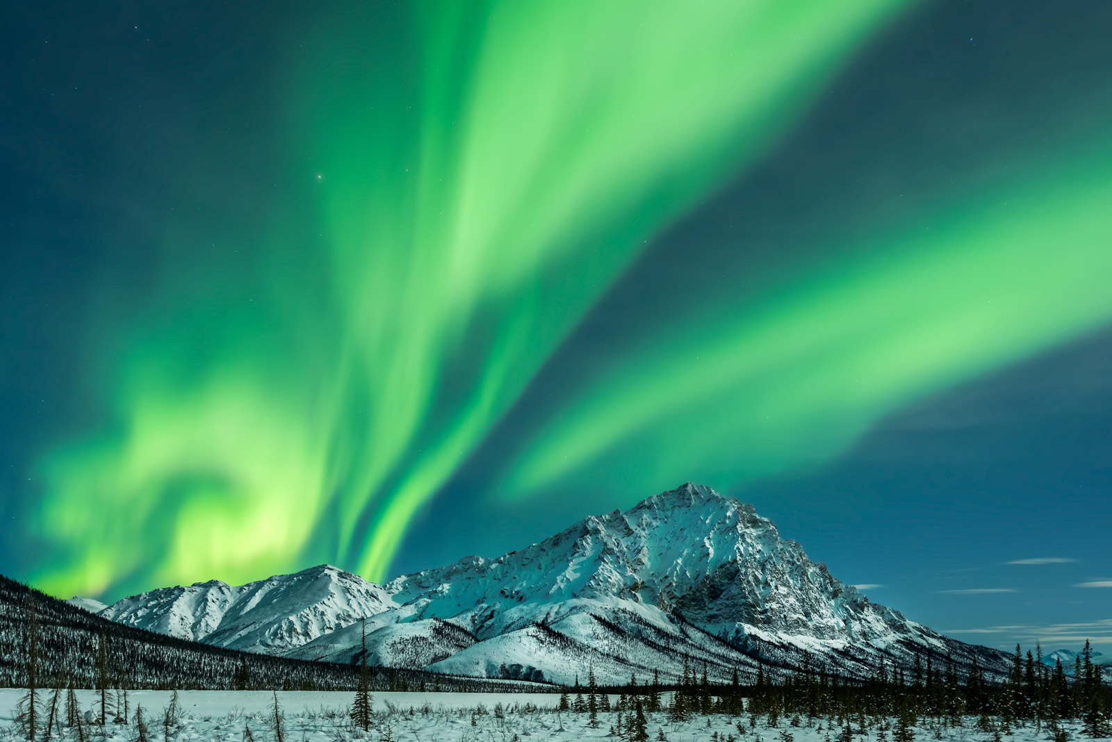 A Limited Edition, Fine Art photograph of the Northern Lights creating a stunning scene over the snow covered mountains of the...