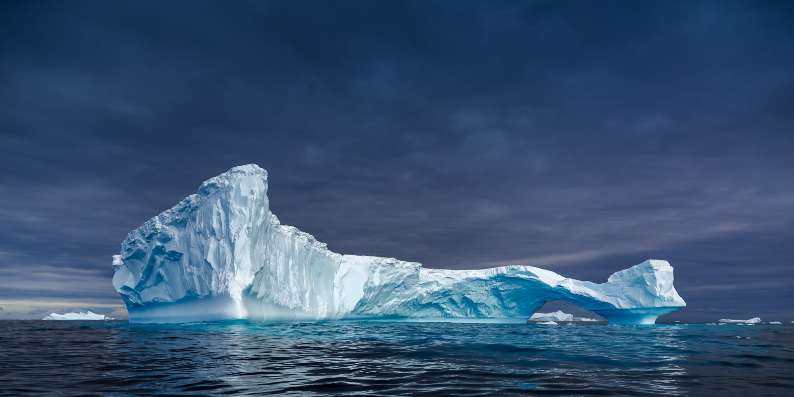 A Limited Edition, Fine Art photograph in Antarctica of a majestic crown shaped iceberg floating in a calm bay and set against...