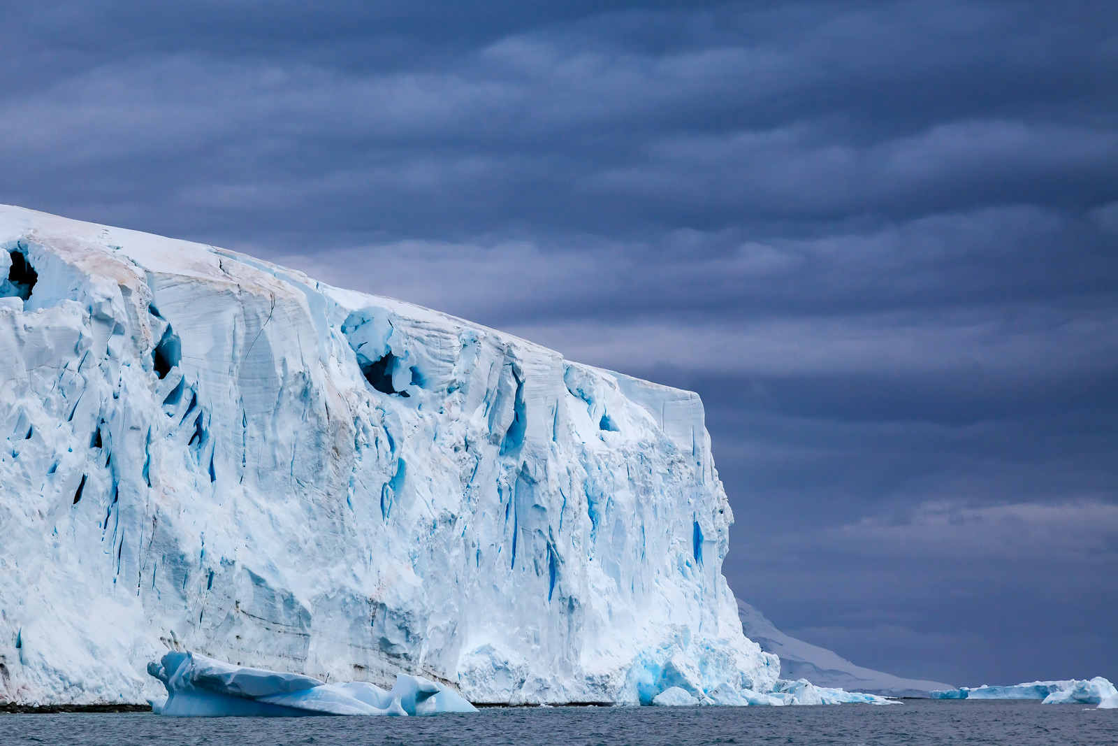 A Limited Edition, Fine Art photograph in Antarctica of the end of a huge iceberg set against stormy dark skies.  Available as...