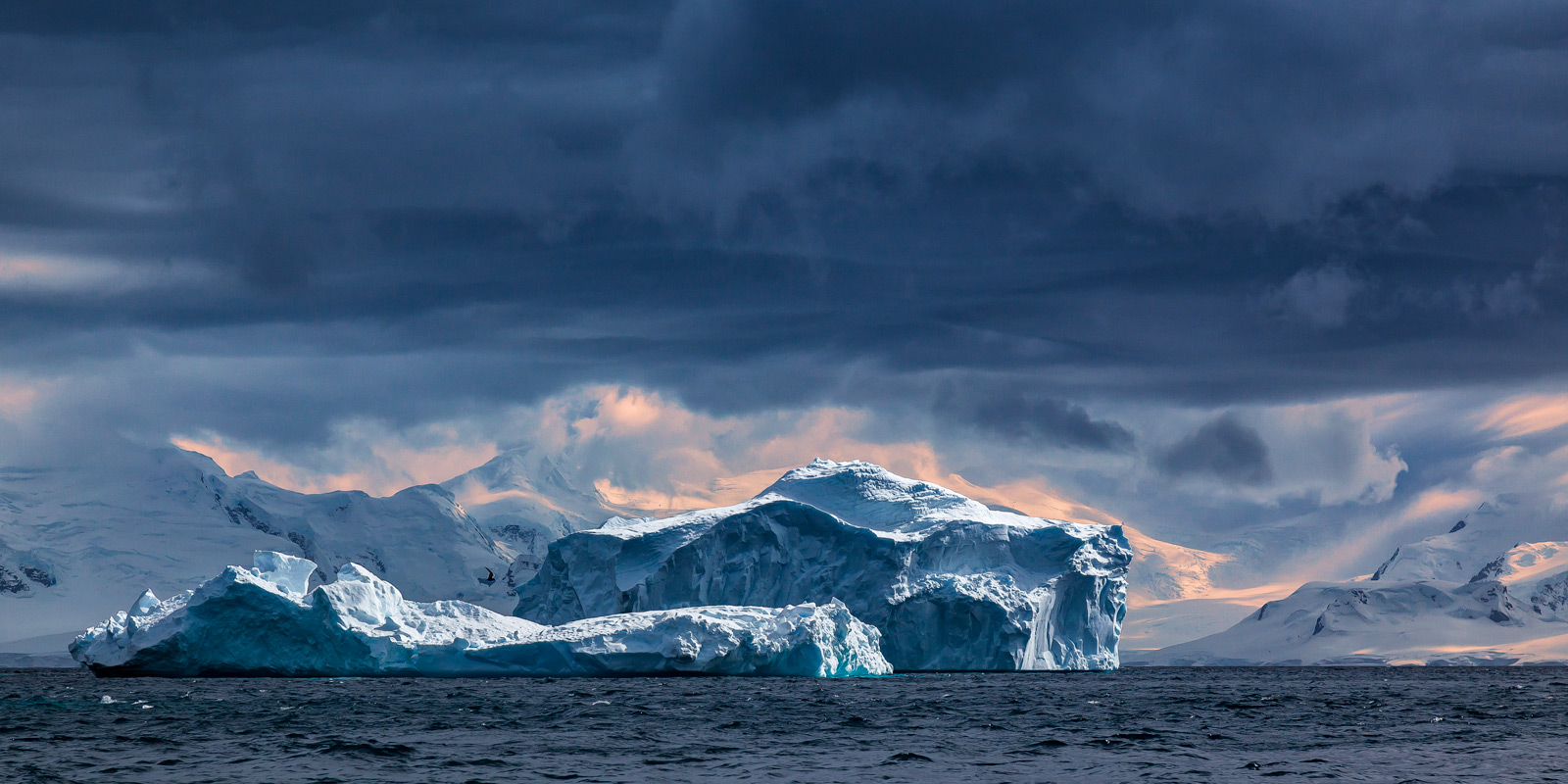 A Limited Edition, Fine Art photograph in Antarctica of a dramatic scene of two massive icebergs floating in a bay near Cuverille...