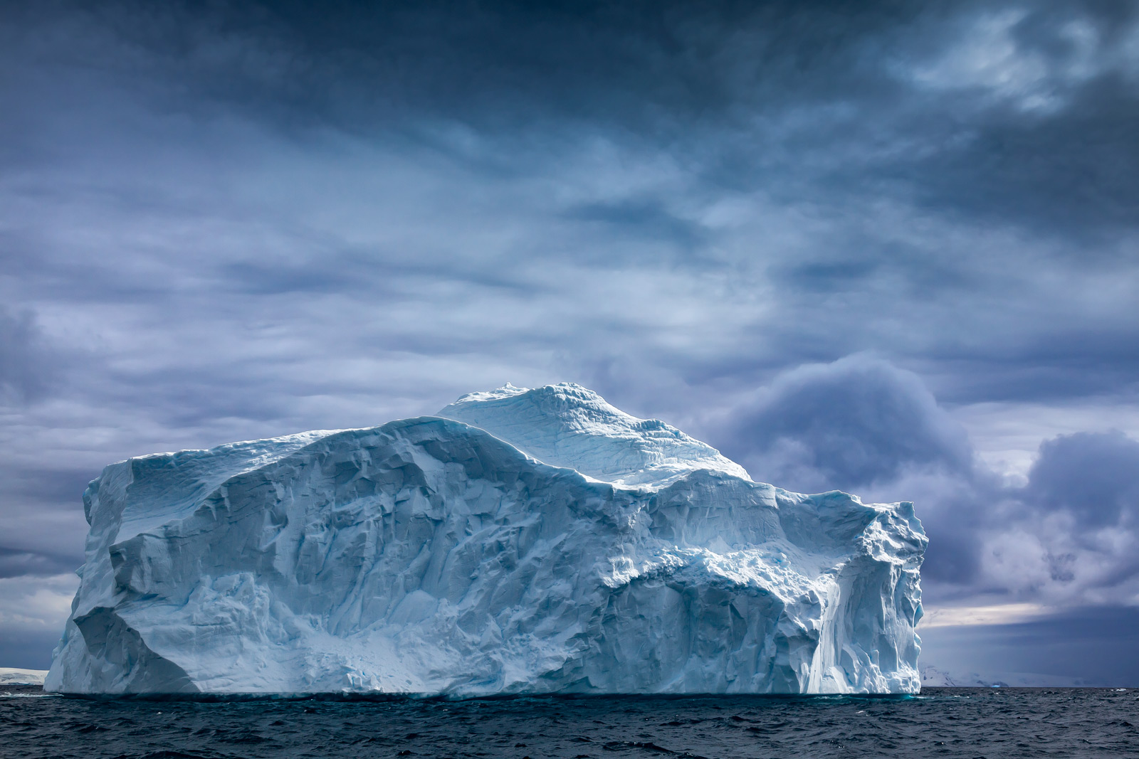 A Limited Edition, Fine Art photograph in Antarctica of a dramatic scene of a massive iceberg set against dark skies at Cuverville...
