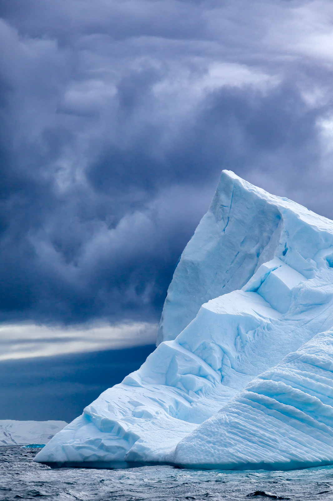 A Limited Edition, Fine Art photograph in Antarctica of an angular iceberg rising into the dark storm clouds near Cuverville...