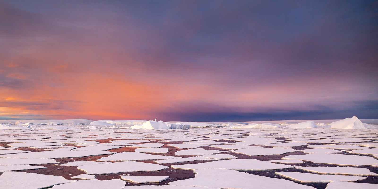 A Limited Edition, Fine Art photograph in Antarctica of the icepack set against the many colors of a brilliant sunrise in the...