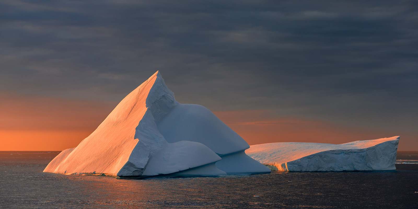 A Limited Edition, Fine Art photograph in Antarctica of a pyramid shaped iceberg during sunset resulting in shades of warm, orange...