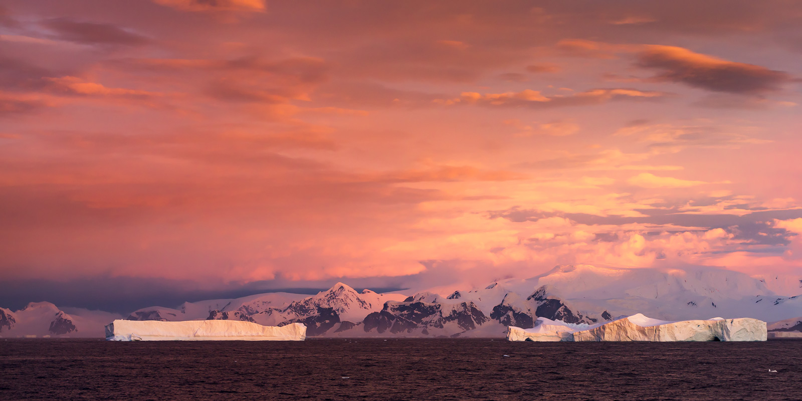 A Limited Edition, Fine Art photograph in Antarctica of a massive tabular iceberg set against a very colorful sunset sky in the...