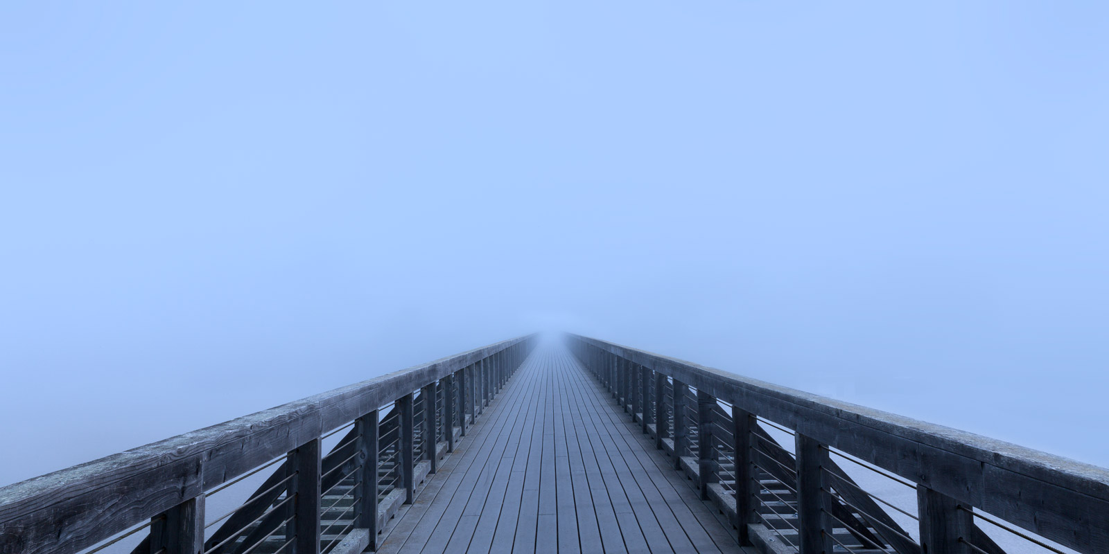 A Limited Edition, Fine Art photograph of a vanishing point of a long footbridge disappearing into the fog on the California...