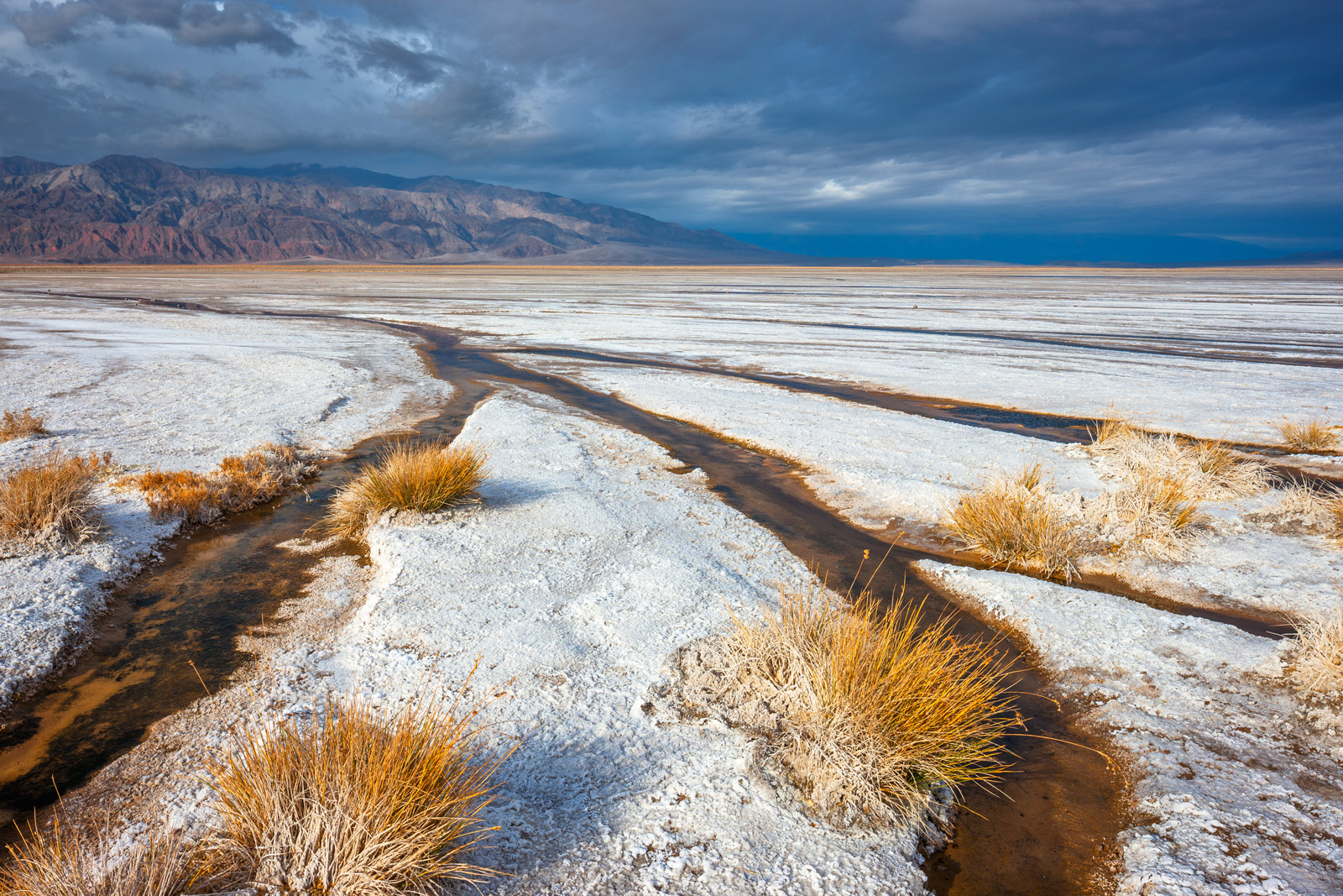 A Limited Edition, Fine Art photograph of an incoming storm over the colors and contrasts of Salt Creek flats in Death Valley...