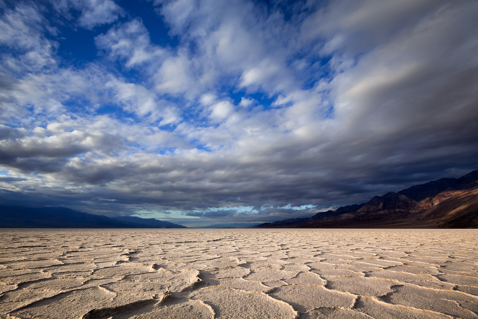 A Limited Edition, Fine Art photograph of Badwater Basin and the formations in the floor of the salt flats under rapidly changing...