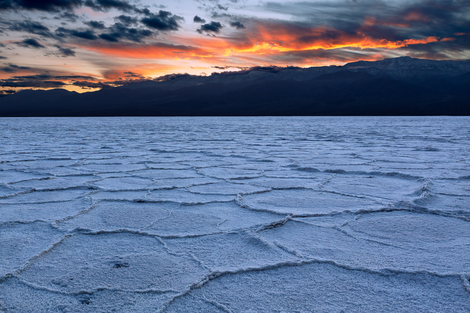 A Limited Edition, Fine Art photograph of a firey sunset above the geometric patterns in the floor of the salt flats of Badwater...