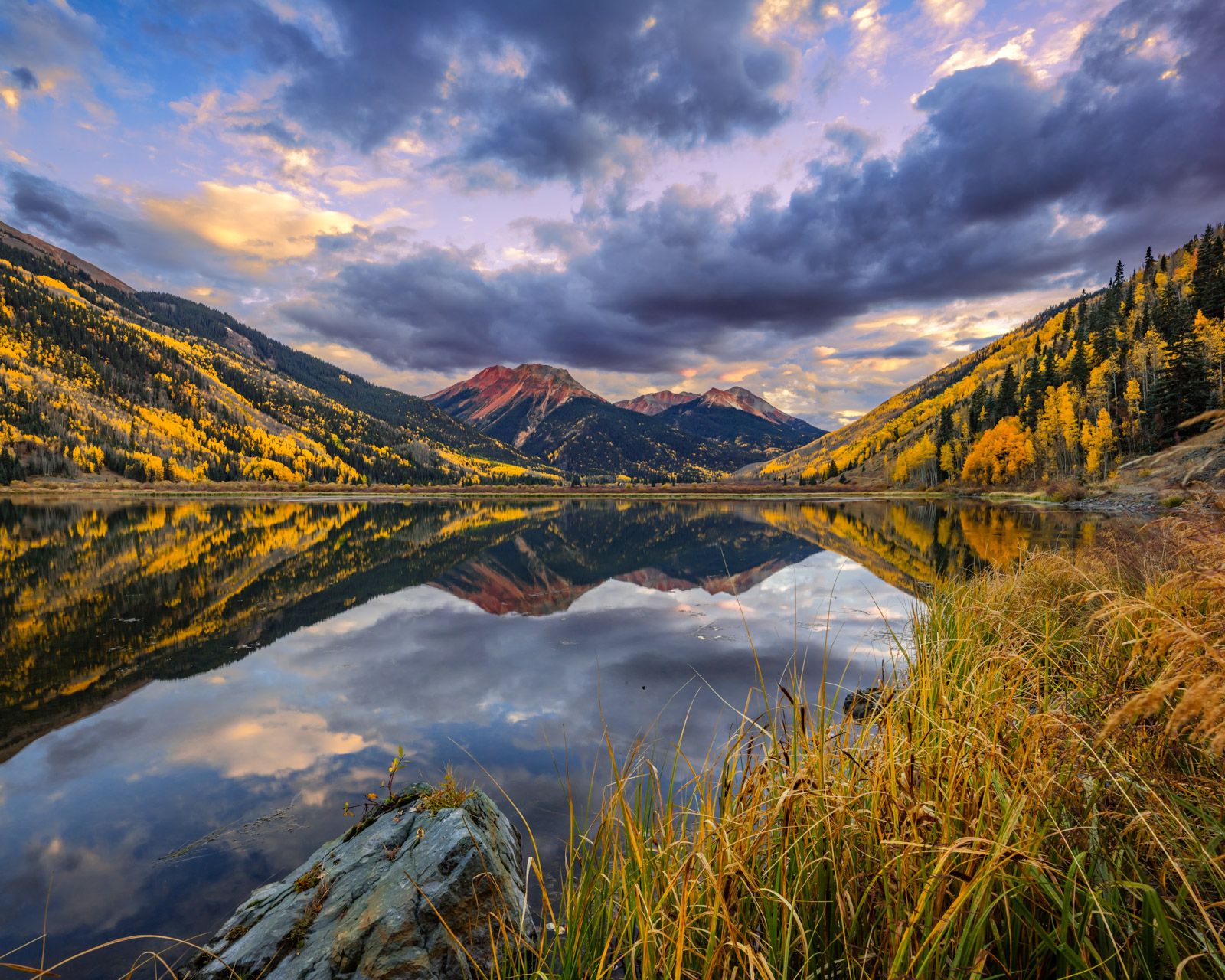 A Limited Edition, Fine Art photograph of Red Mountain and Fall Aspen trees reflecting perfectly in Crystal Lake at sunrise in...