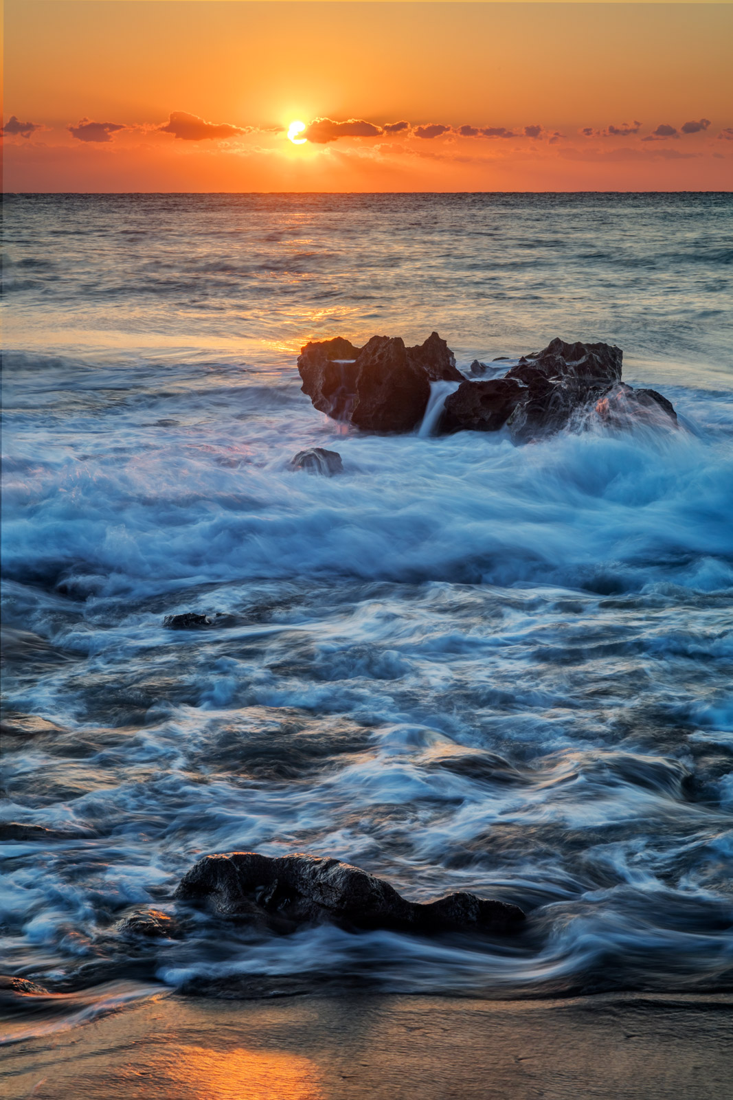 A Limited Edition, Fine Art photograph of a Florida sunrise over the rocky Atlantic Coast and swirling waves at Coral Cove, Florida...