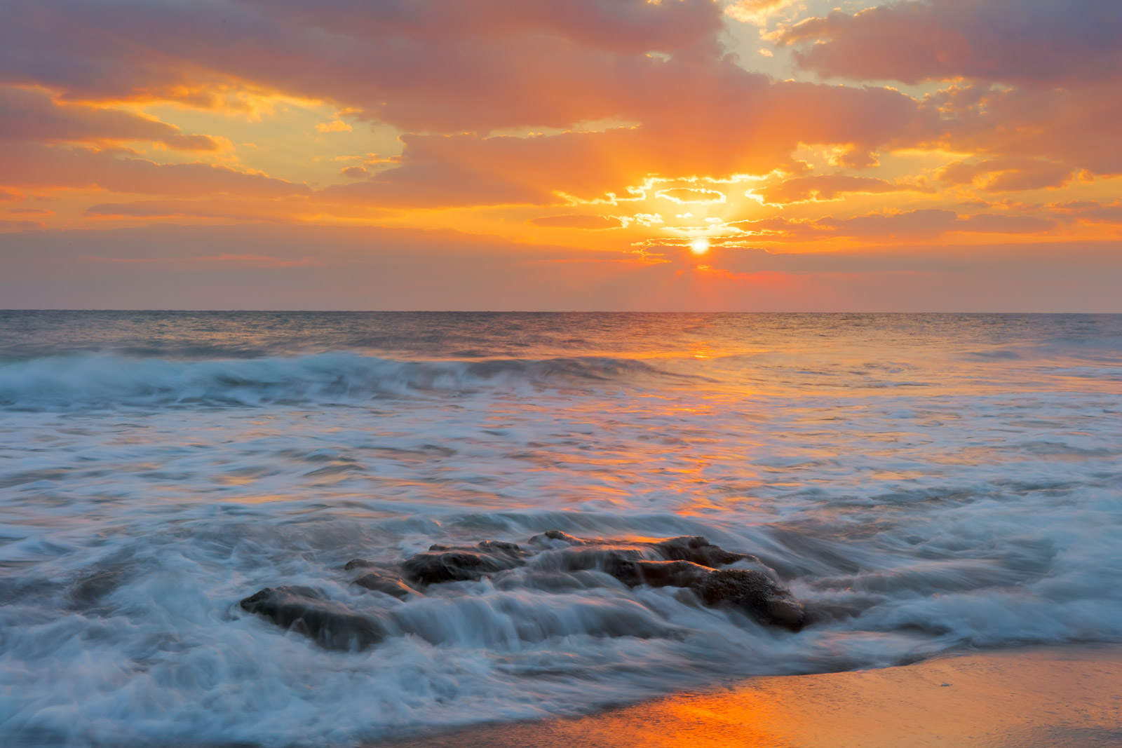 A Limited Edition, Fine Art photograph of a colorful sunrise and soft beams of the sun lighting up the waves washing over the...