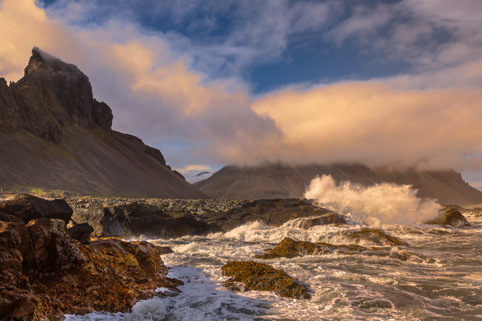A Limited Edition, Fine Art photograph of waves exploding on the rocky coast of Iceland with mountains in the background.  Available...