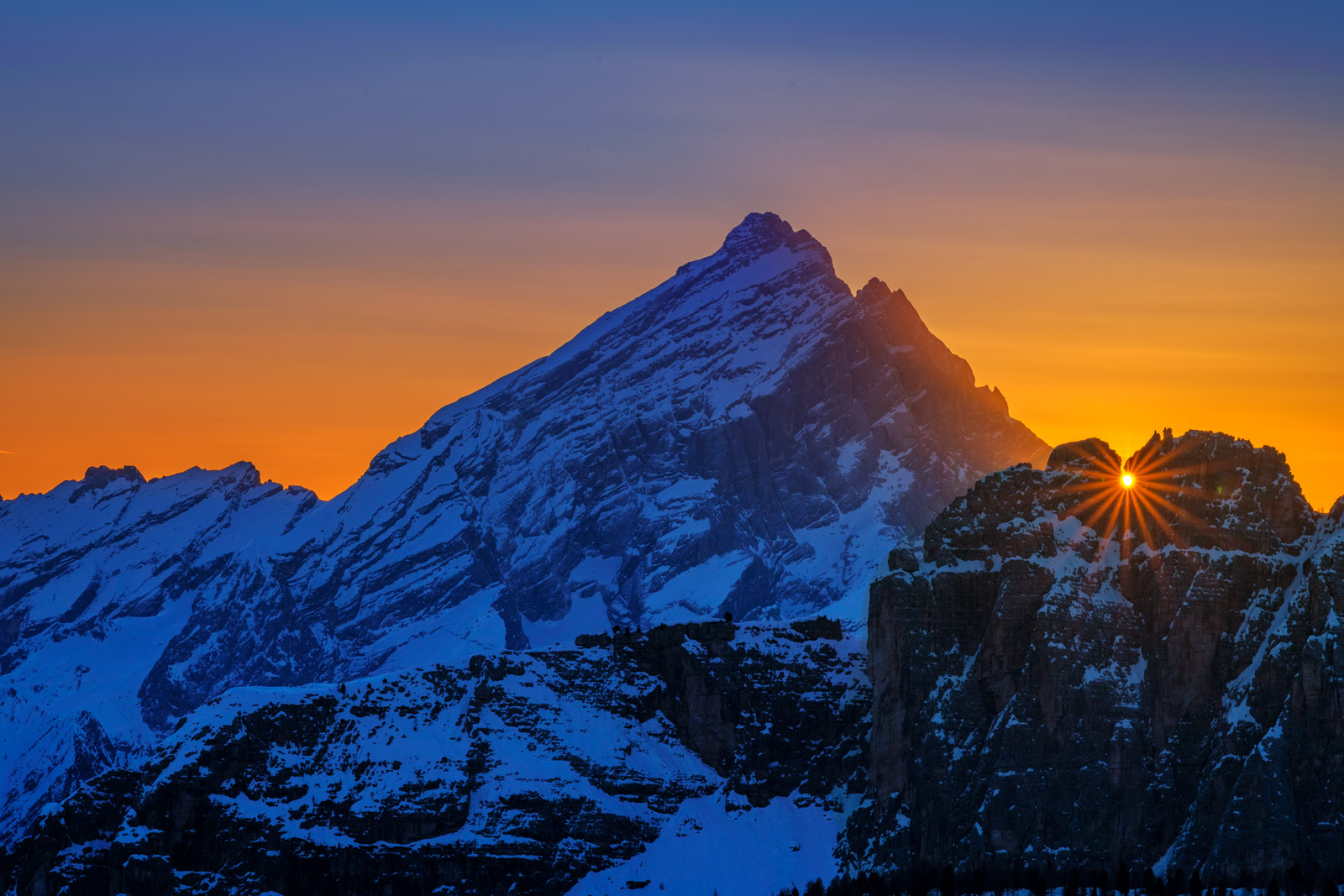 A Limited Edition, Fine Art photograph of the sun bursting over the horizon next to snow covered mountains during winter in the...
