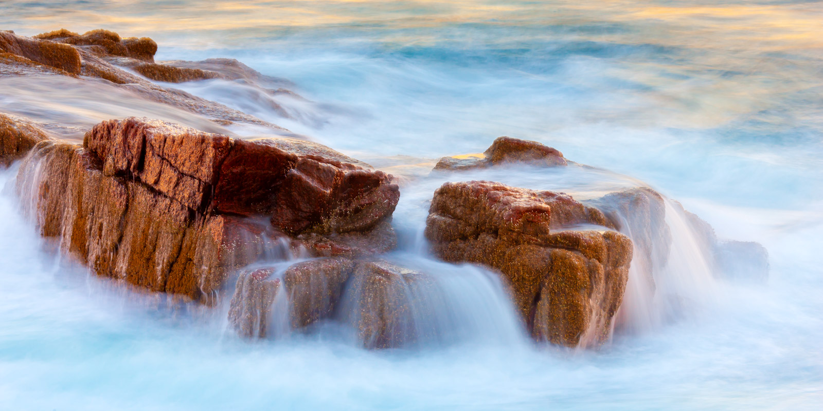 A Limited Edition, Fine Art long exposure photograph of ocean water flowing gently over the rocks at Acadia National Park in...