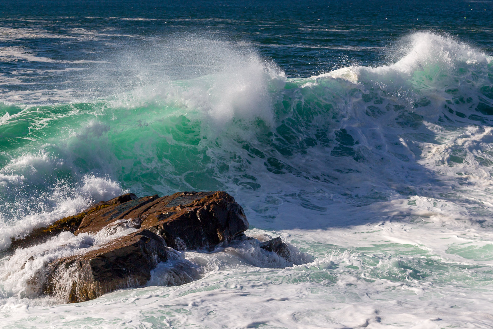 A Limited Edition, Fine Art photograph of large, colorful green and aqua storm waves breaking over rocks at Acadia National Park...
