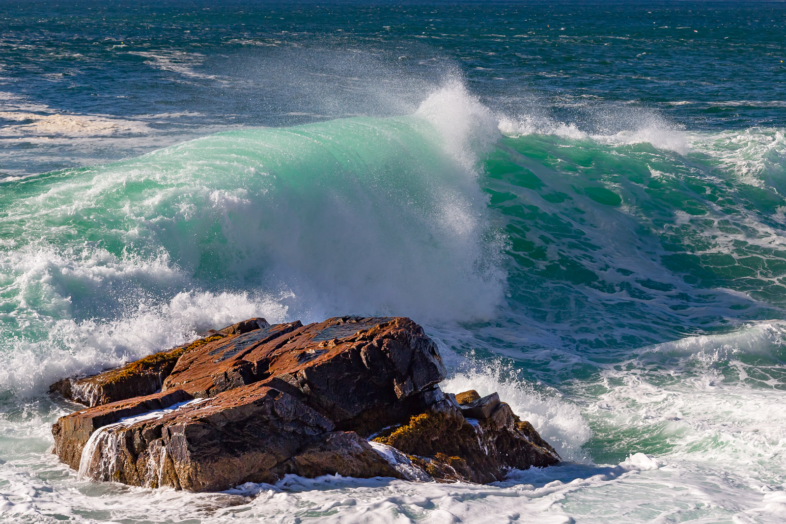 A Limited Edition, Fine Art photograph of a large green and aqua storm wave breaking over rocks at Acadia National Park in Maine...