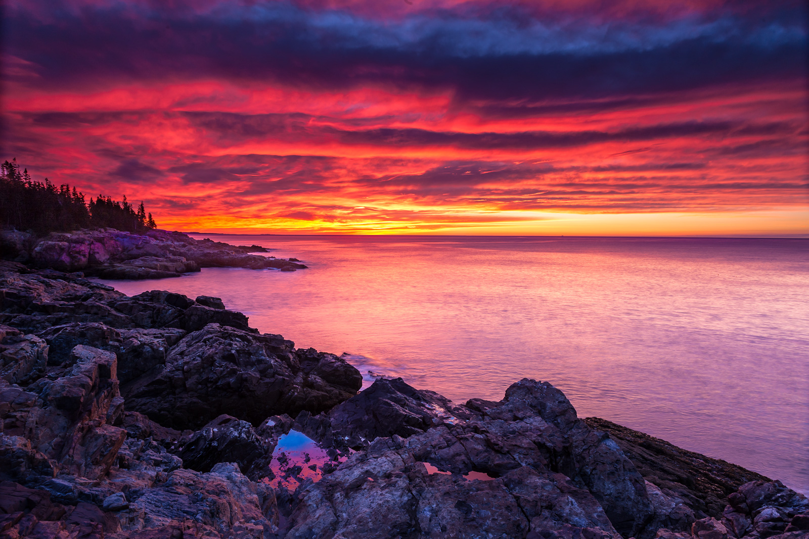 A dramatic red sunrise over the rocky coast of the Atlantic ocean at Acadia National Park on the Maine Coast.