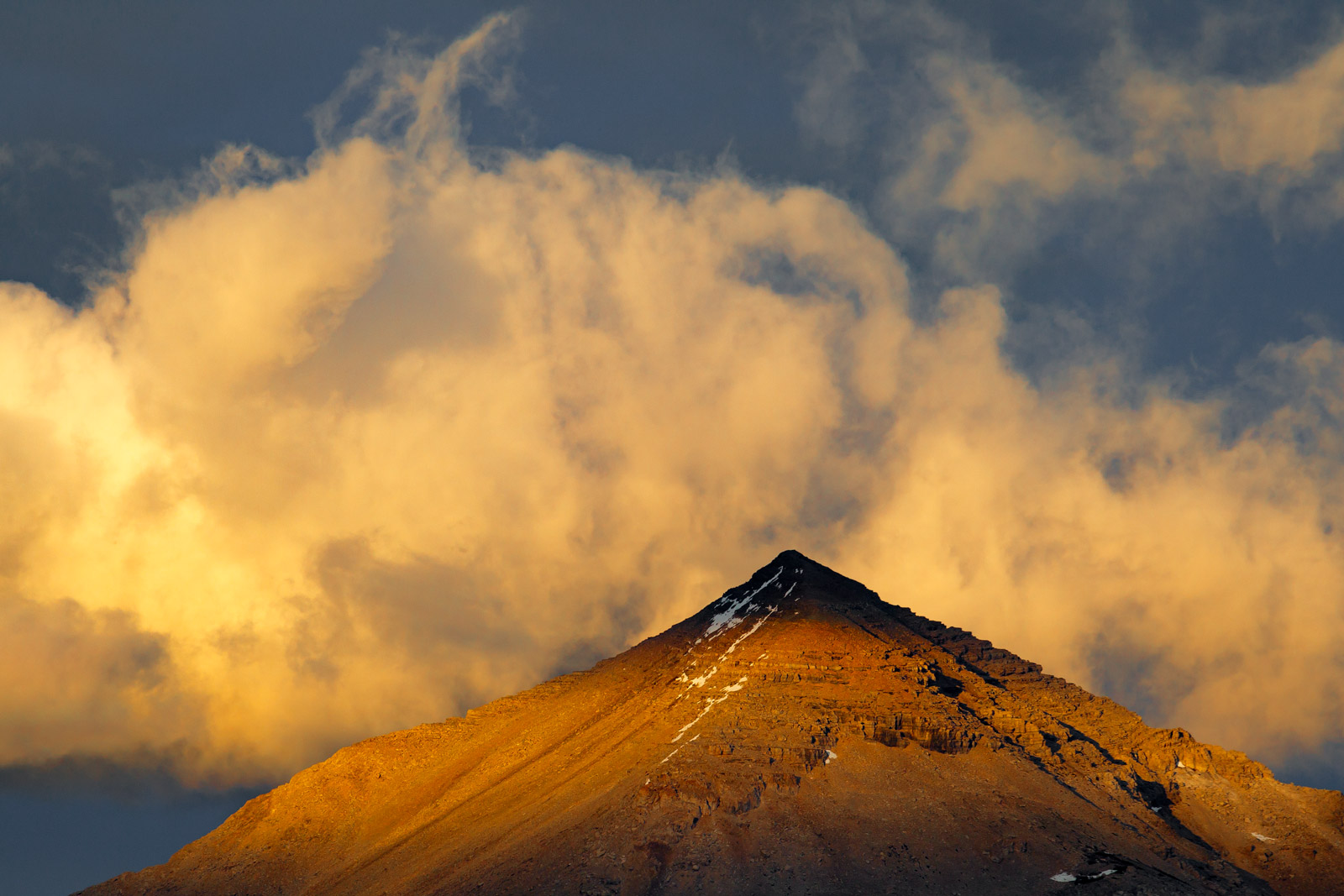 A Limited Edition, Fine Art Photograph of dramatic clouds bursting at sunset over Divide Mountain in Glacier National Park in...