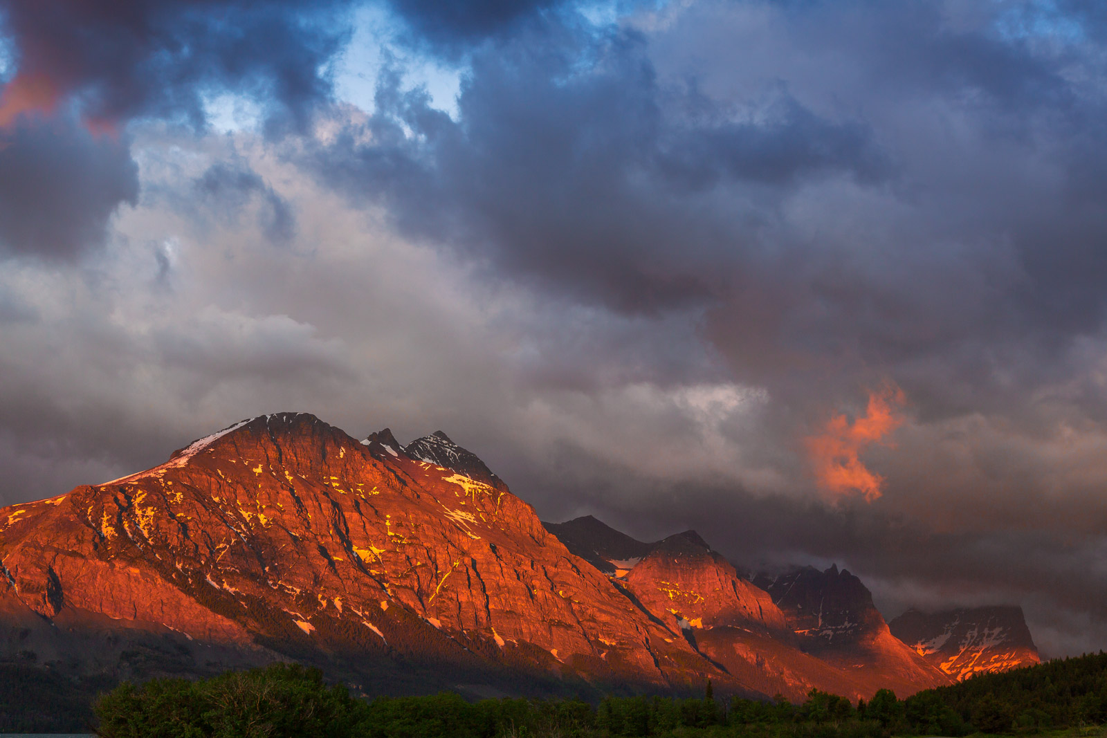 A Limited Edition, Fine Art photograph of spectacular sunrise light and storm clouds on the mountains at Glacier National Park...