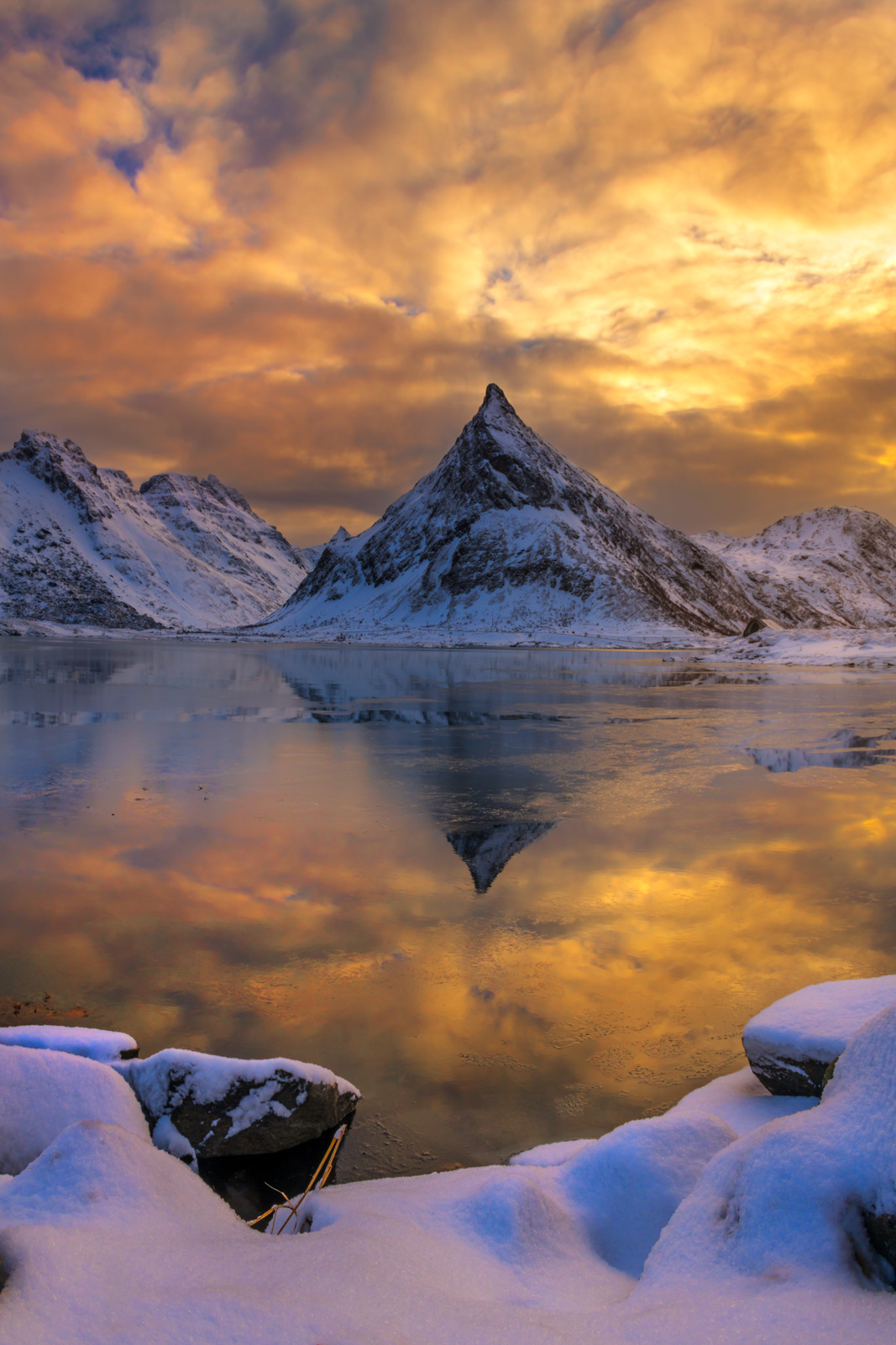 A Limited Edition, Fine Art photograph of the point of a snow covered mountain dramatically reflecting  in the water at sunset...