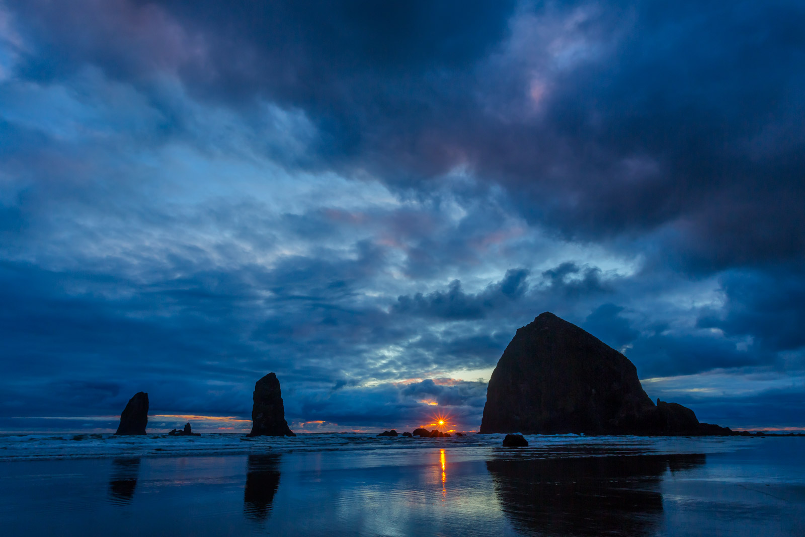 A Limited Edition, Fine Art photograph of Haystack Rock with the light of a dramatic sunburst and sunset at the sea stack in...