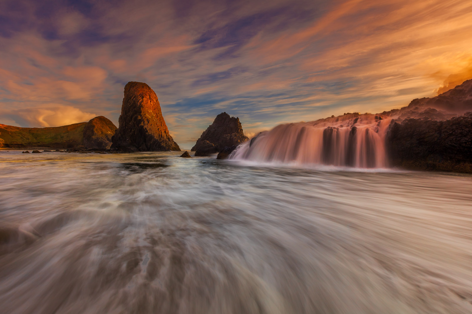 A Limited Edition, Fine Art photograph of a gorgeous sunset with a flow of water over the rocks on the Oregon coast in Newport...
