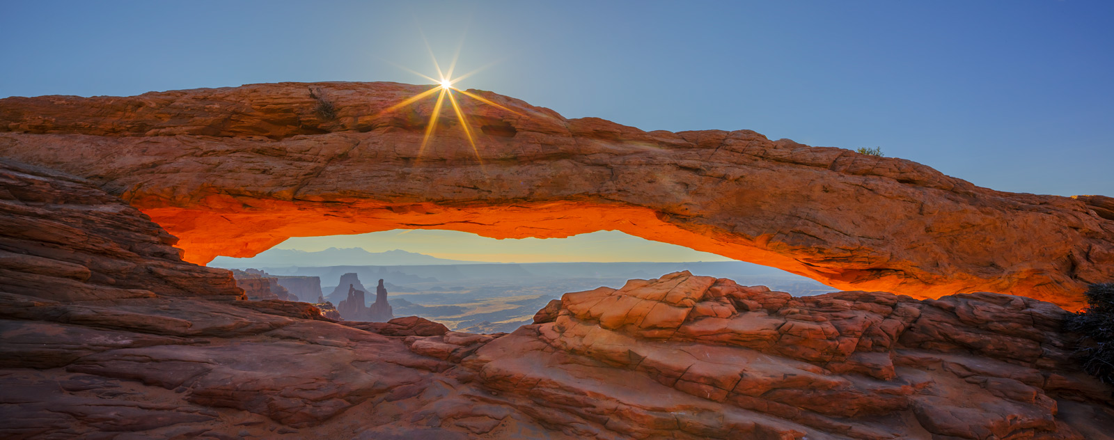 A Limited Edition, Fine Art panoramic photograph of Mesa Arch with an impressive sunburst just above Mesa Arch at Canyonlands...