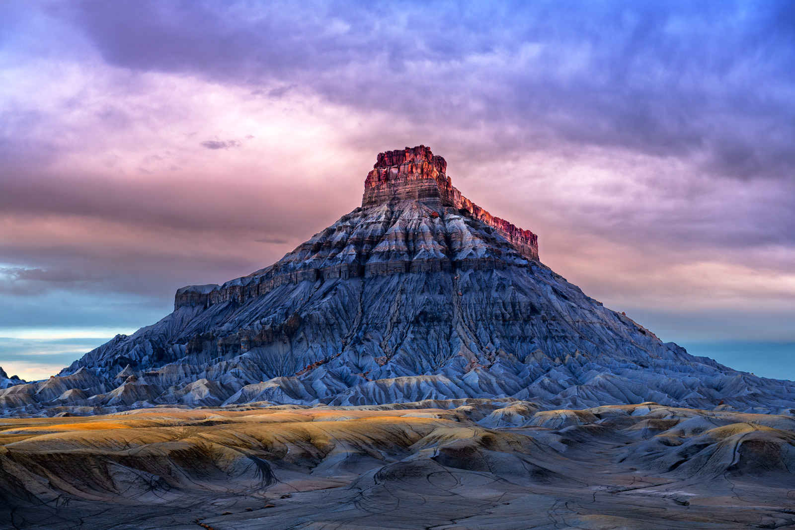 A Limited Edition, Fine Art photograph of Factory Butte in the Desert Southwest reflecting many colors caused by early sunrise...