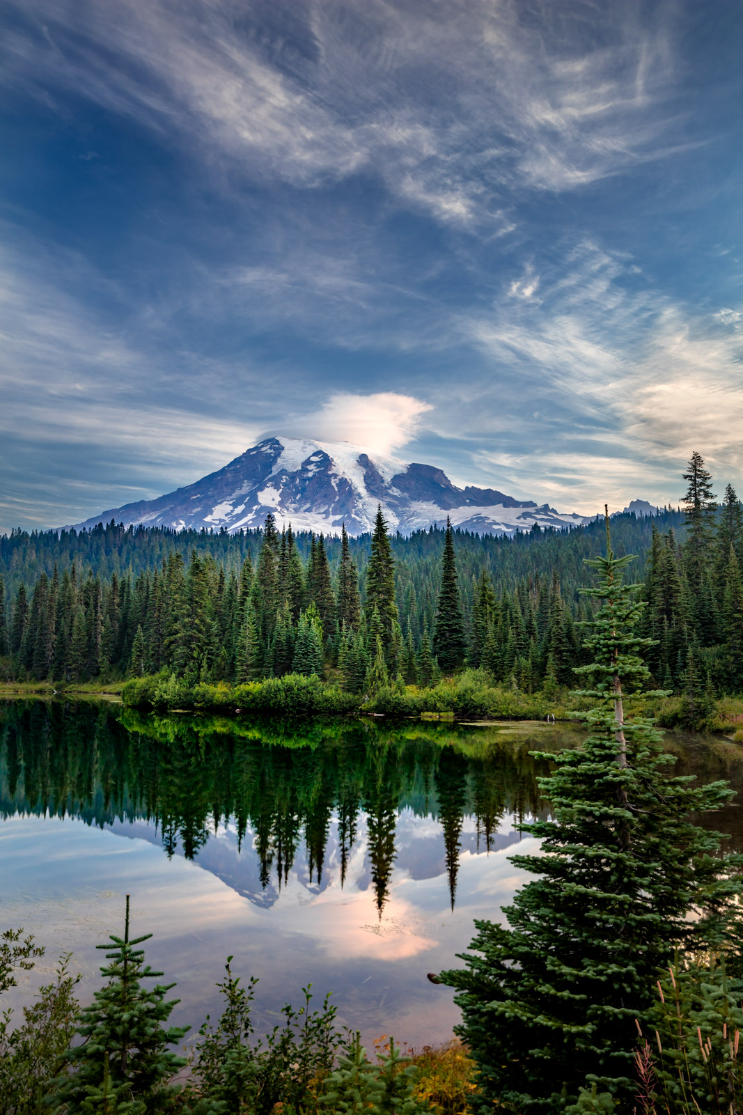 A Limited Edition, Fine Art photograph of Mount Rainier reflecting in Reflection Lakes framed by beautiful pine trees.  Available...