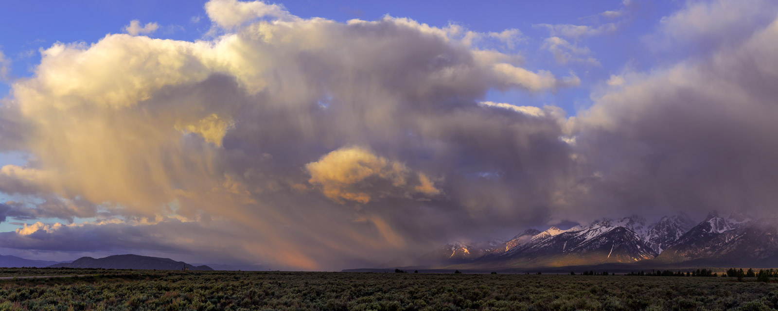 A Limited Edition, Fine Art photograph of a massive storm cloud looking like the mother ship over the mountains at Grand Teton...